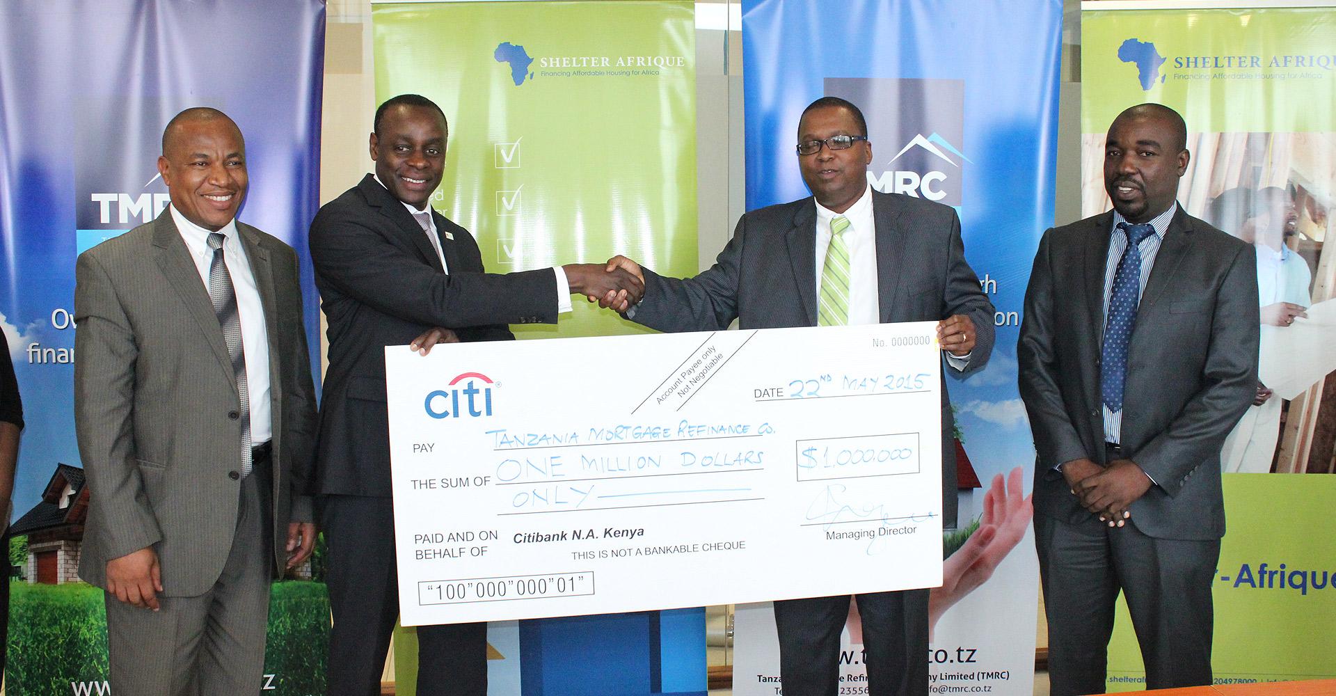 Mkurugenzi Mtendaji wa Taasisi ya mikopo ya nyumba ya Tanzania Mortgage Refinance (TMRC), Oscar Mgaya (kulia) akipokea jijini Dar es Salaam, mfano wa hundi ya Dola za Kimarekani milioni moja